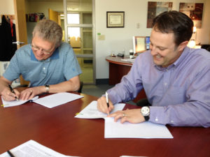Gary Madsen and Michael Dixon signs licensing agreement at UNeMed.