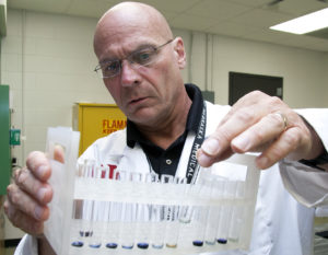 UNMC researcher Sam Sanderson, Ph.D., checks the results of a recent quality control test at his Omaha lab. His startup company, Prommune, has scheduled a test for a new H1N1 vaccine on pigs in Aug. 2015.
