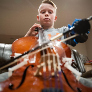 Brendan Sullivan/Omaha World-Herald Lincoln fourth-grader Peyton Tiernan can now play the cello with a prosthesis design by a UNO team — am arm with a clamp on the end that locks onto the bow. Read the full article at: https://www.omaha.com/livewellnebraska/inspiration/lincoln-boy-learns-cello-with-help-from-a-uno-designed/article_5baf4226-d347-5e6e-a95b-ae1273b6a3a3.html